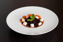 Risotto noir avec du fromage, menthe décorée du plat blanc images stock