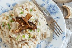 Risotto with porcini mushrooms o. N a blue plate on a wooden table royalty free stock photos