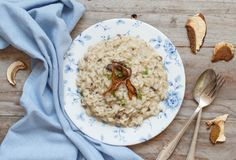 Risotto with porcini mushrooms on a blue plate. On a wooden table royalty free stock photography