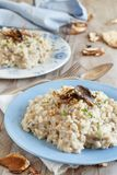 Risotto with porcini mushrooms on a blue plate. On a wooden table royalty free stock image