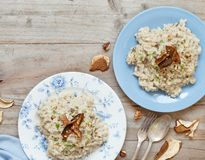 Risotto with porcini mushrooms on a blue plate. On a wooden table stock image