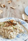 Risotto with porcini mushrooms on a blue plate. On a wooden table stock photography