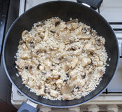 Risotto preparation. Risotto with chicken and mushrooms preparation in saucepan Stock Images