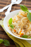 Risotto with pumpkin and onion in a white bowl,. Basil Stock Image