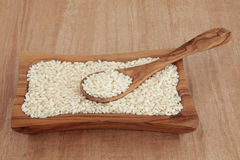 Risotto Rice. Risotto arborio short grain rice in an olive wood bowl with spoon over papyrus background Royalty Free Stock Image