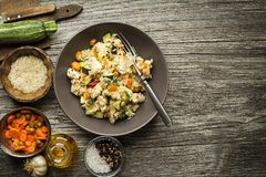 Risotto. With chicken and vegetables served on wooden table Stock Photography