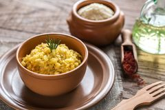 Risotto with saffron and parmesan. Portion of risotto with saffron on the wooden table Royalty Free Stock Image