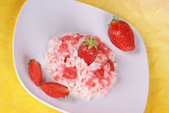 Risotto with strawberries. Served on a white plate. Studio shot over yellow background Stock Images
