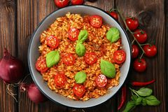 Risotto with tomatoes, fresh herbs and parmesan cheese. And basil stock photo