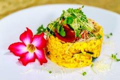 Risotto végétarien avec le potiron, la courgette, le parmesan, l'oignon coloré avec du jus de betteraves et les pousses de harico photos stock