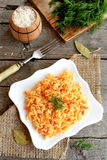Risotto with vegetables on plate. Rice cooked with carrots, tomatoes, garlic and spices royalty free stock photos
