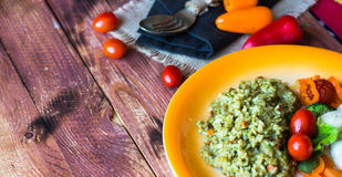Risotto with vegetables, on wooden background stock photo