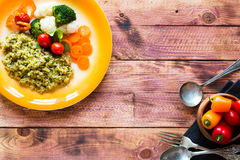 Risotto with vegetables, on wooden background royalty free stock photography