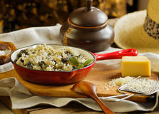 Risotto with  wild mushroom served  red pan as traditional Itali Stock Photos