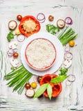 Risottorismaträtt och olika grönsaker och smaktillsatsingredienser för smaklig vegetarisk matlagning på ljus lantlig träbackgrou arkivbild