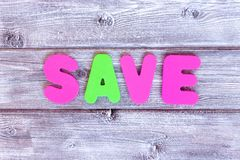 Risparmi del messaggio fatti delle lettere variopinte su fondo di legno rustico d'annata immagini stock libere da diritti