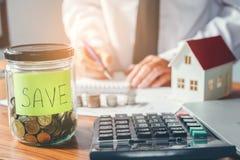 Risparmio, calcolatore di finanze che conta soldi per il concetto domestico immagini stock