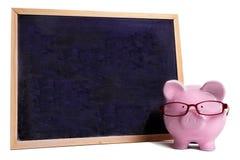 Risparmio concetto, vetri d'uso di insegnamento superiore del porcellino salvadanaio con la piccola lavagna in bianco, isolata Immagini Stock Libere da Diritti