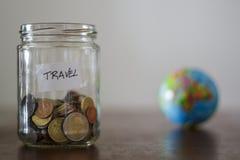 Risparmio dei soldi di viaggio in un barattolo di vetro con il globo della terra sui precedenti fotografia stock libera da diritti