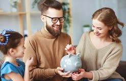 Risparmio della famiglia, pianificazione del bilancio, il denaro per piccole spese dei bambini Famiglia con la banca piggy immagine stock libera da diritti