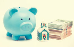 Risparmio di vendita del bene immobile, mercato di prestiti Casa del porcellino salvadanaio e mucchio di euro contanti Immagini Stock
