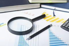 Risparmio domestico, concetto del bilancio Grafico, penna, calcolatore e lente d'ingrandimento sulla tavola di legno dell'ufficio fotografia stock libera da diritti
