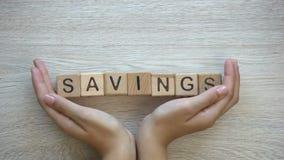 Risparmio, mani che spingono parola sui cubi di legno, pianificazione del bilancio familiare, economia archivi video