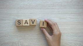 Risparmio, mano che mette parola sui cubi di legno, pianificazione del bilancio familiare, economia archivi video