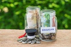 Risparmio per il concetto di istruzione come monete in barattolo con istruzione del testo fotografie stock