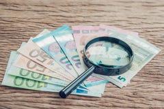 Risparmio, tassa, investimento o ricerca di finanza il concetto del rendimento, vetro della lente sul mucchio di euro banconote s fotografie stock