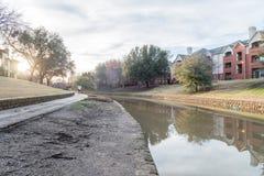 Rispecchi la riflessione del complesso di costruzione dell'appartamento della riva del fiume al tramonto Immagine Stock Libera da Diritti