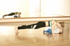 Rispecchiare giovane madre che gode del exercice nello studio di forma fisica con il suo neonato Immagini Stock