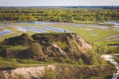 Risque a garganta com a família feliz na parte superior Vista bonita no beira-rio inundado da mola meander Processamento do filme foto de stock