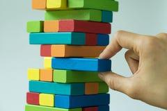 Risque ou concept de stabilité avec la main tirant le blo en bois coloré Image stock