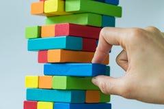 Risque ou concept de stabilité en tant que main femelle tirant en bois coloré Photographie stock libre de droits