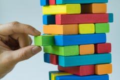 Risque ou concept de stabilité en tant que main femelle tirant en bois coloré Images libres de droits