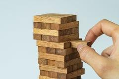 Risque ou concept de stabilité en tant que main femelle tirant le bloc en bois franc Photographie stock libre de droits