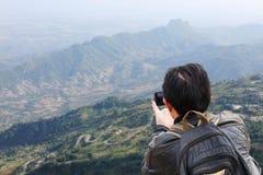 Risquez l'homme avec le dispositif ou le téléphone de généralistes dehors dans la région sauvage ex Photographie stock