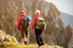 Risquez, voyagez, tourisme, hausse et concept de personnes - couple de sourire marchant avec des sacs à dos dehors image libre de droits