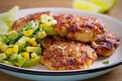 Rissóis caseiros ou hamburgueres da galinha com salsa do milho do abacate imagem de stock