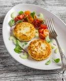Rissóis da batata e salada fresca do tomate e do aipo em uma placa cerâmica leve Fotografia de Stock