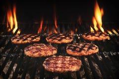 Rissóis grelhados BBQ dos hamburgueres na grade flamejante quente Fotos de Stock Royalty Free