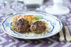Rissóis triturados do hamburguer da bola de carne da carne com alguma salada no lado Imagem de Stock