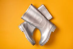 Сriss-cross gumboots. Autumn creative shot: stylish silver gumboots composed criss-cross on orange background. Top view. Flat lay Royalty Free Stock Photos