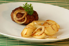 Rissole with grilled potato and onion Stock Image