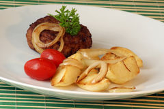 Rissole with grilled potato and tomato Stock Photo