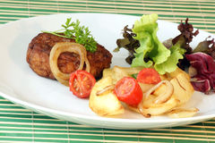 Rissole with grilled potato and tomato Stock Images