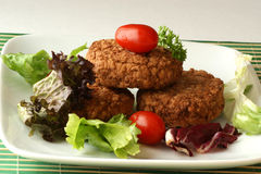 Rissole with plum tomato and salad Royalty Free Stock Images