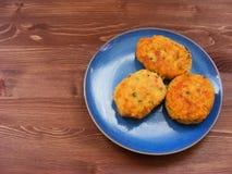 Rissoles ветчины, сыра и картошек на голубой плите на деревенской деревянной предпосылке Стоковые Изображения