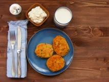 Rissoles ветчины, сыра и картошек на голубой плите, молока в стекле, перц-бака и сметаны в деревянном шаре на деревенской предпос Стоковые Фото